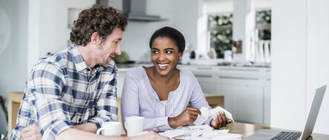 A smiling couple looks through receipts at their kitchen table.
